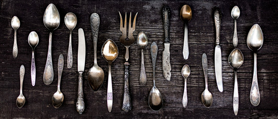 Vintage cutlery - spoons, forks and knives on an old wooden background. Wall mural