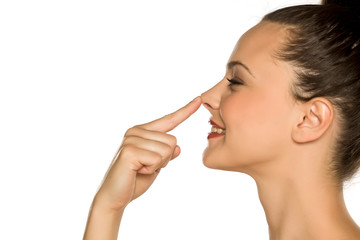 profile of young happy woman touches her nose with her finger on a white background