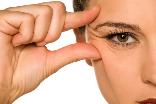 young woman pinching her eye wrinkles with her fingers on a white background