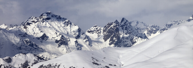 Fototapete - Snowy off-piste slope and mountains in clouds