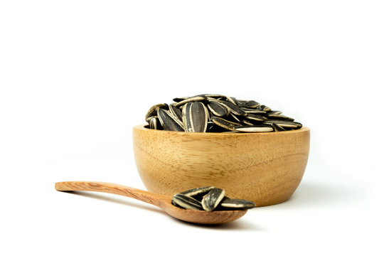 Close up of sunflower seeds isolated in wooden bowl against and spoon on white background and clipping path.