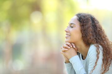 Happy mixed race woman meditating outdoors
