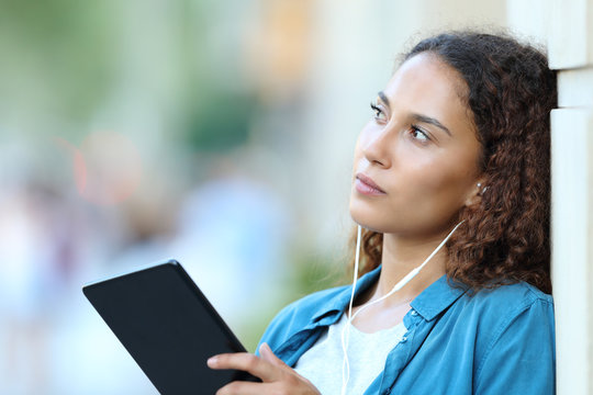 Serious mixed race woman thinking listening to music