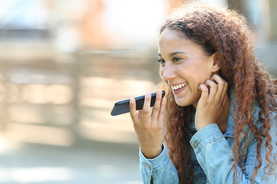 Mixed-race woman using voice recognition on phone