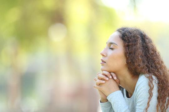 Serious mixed race woman meditating outdoors