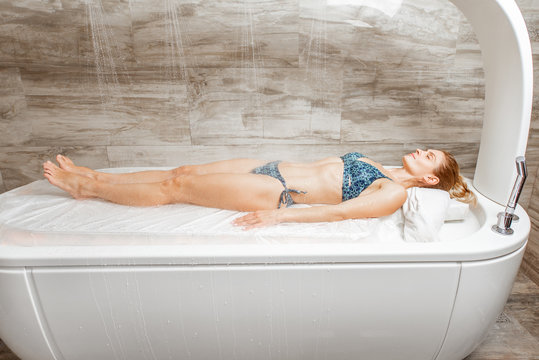 Woman lying under the hot shower in the spa