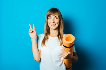 A young woman in a white T-shirt holds a yoga mat and makes a hand gesture on a blue background....