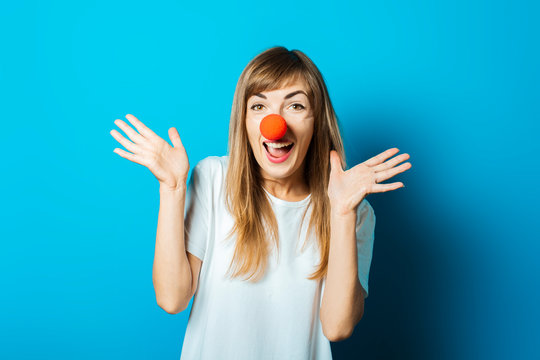 Beautiful young woman in a white T-shirt and a red clown nose smiles and makes hand gestures on a blue background. Concept party, costume, red nose day