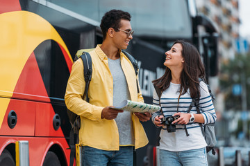 Woman with digital camera smiling to mixed race friend with map and backpack