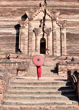 novice buddhist monks with red traditional robes holding red umbrellas walking in a brown buddhist temple in myanmar