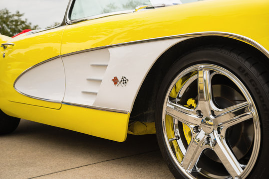A front wheel and side details of a yellow 1958 Corvette Chevrolet classic car on October 21, 2017 in Westlake, Texas. Closeup.