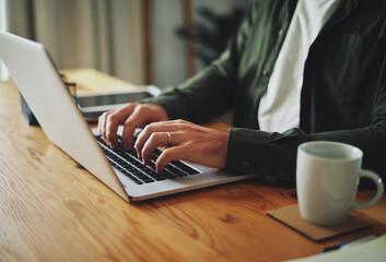 Man typing on laptop computer keyboard at table