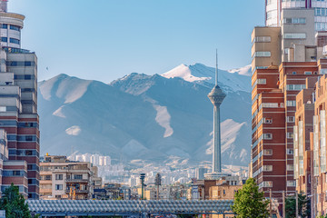 06/05/2019 Tehran,Iran,Famous view of Tehran,Flow of traffic inside, above and nearby round Tohid Tunnel with Milad Tower and Alborz Mountains in Background Wall mural