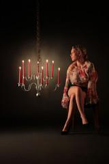 Frau sitzt neben Kerzenleuchter