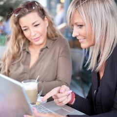 Hübsche junge Frauen mit Laptop bei der Kaffeepause