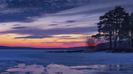 Fotobehang - Beautiful pine trees silhouettes at frozen pond lake, epic colorful sunset sky in background. Timelapse, 4K UHD.