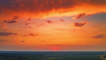 Fotobehang - Aerial view of sunset sun setting above horizon in red sky over forest landscape. Hyperlapse timelapse, 4K UHD.