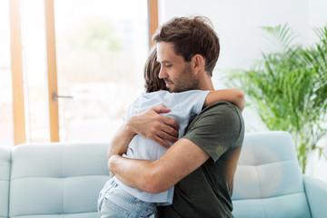 Fototapeta Father embracing son while sitting on sofa at home obraz