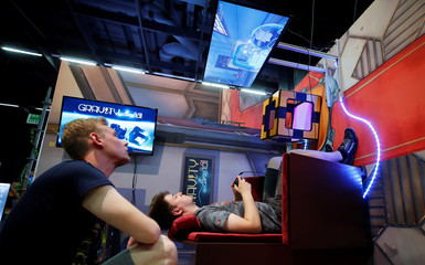 A gamer plays Gravity in a chair hung on the wall during the media day of Europe's leading digital games fair Gamescom, which showcases the latest trends of the computer gaming scene, in Cologne