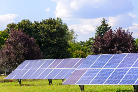Solar panels mounted on the ground. Green grass and blue sky background