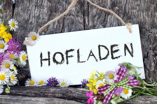 Schriftzug: Hofladen, auf Schild vor Holzhintergrund.