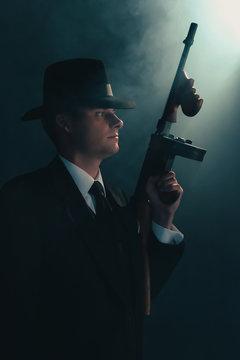 Retro gangster stands with machine gun in mist.