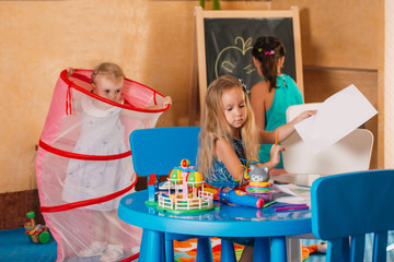 Little cute girls play in the room. Development and social learning