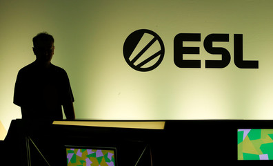 A gamer is silhouetted against an illuminated wall with the logo of the Electronic Sports League ESL during the media day of Europe's leading digital games fair Gamescom, which showcases the latest trends of the computer gaming scene, in Cologne