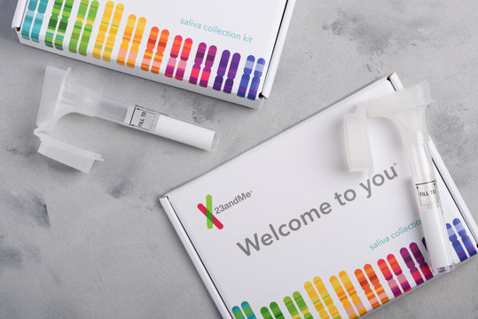 23andMe personal genetic test saliva collection kit, with tube and box on table overhead view.