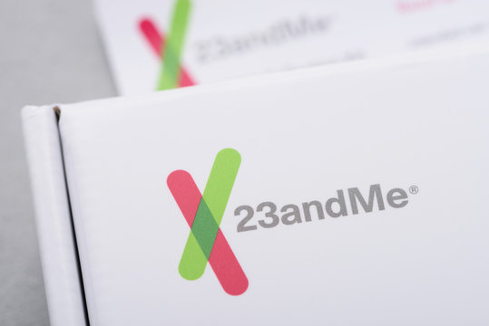 23andMe logo closeup on personal genetic test saliva collection kit. Illustrative editorial.