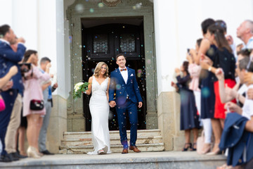 Newlyweds exiting the church after the wedding ceremony, family and friends celebrating their love with the shower of soap bubbles, custom undermining traditional rice bath. Wall mural