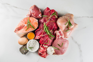 Carnivore diet background. Non vegan protein sources, Different meat food - chicken breast, pork steak, beef tenderloin, eggs, spices for cooking. White marble background copy space - fototapety na wymiar