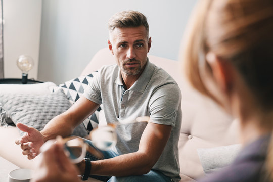 Photo of brooding handsome man having conversation with psychologist in room