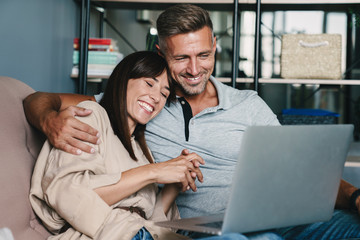 Photo of beautiful caucasian couple smiling while watching laptop on sofa at home