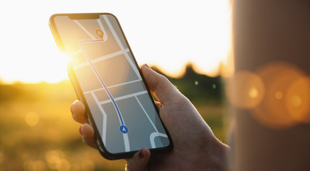Tourist using GPS map navigation app on smartphone screen to get direction to destination address in the landscape, travel and technology concept image
