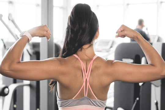 Woman flexing her muscles from back