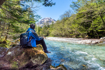 Man sit alone on rock near Azusa river at Kamikochi in Northern Japan Alps.