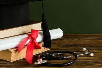 Mortarboard, textbooks, graduation scroll tied with red ribbon and stethoscope