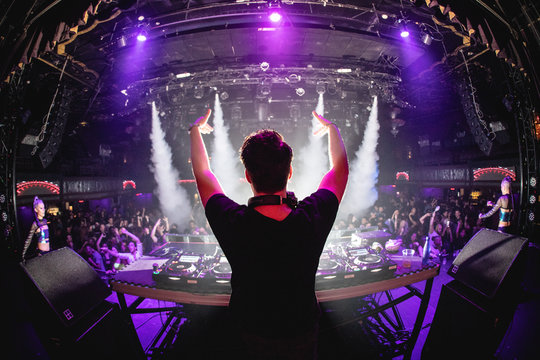 DJ in nightclub with hands up and cryo canons, shot from behind
