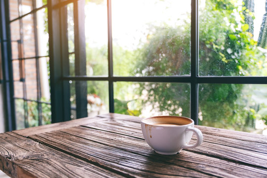 A white mug of hot coffee on wooden table in the morning