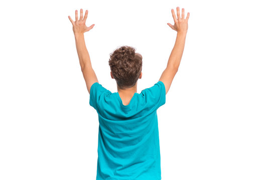Back view of teen boy holding hands up and celebrating success. Cheerful teenager in blue T-shirt celebrating something - rear view. Happy child isolated on white background.