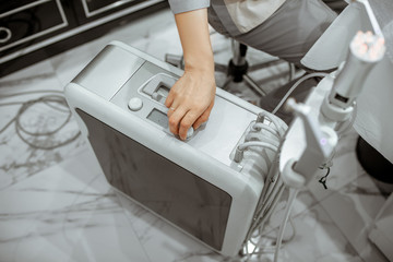 Cosmetologist working with oxygen mesotherapy machine at the salon, close-up view