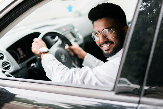 Young handsome man in his new black gray car, relaxing, hand on steering wheel, looking out window from vehicle.