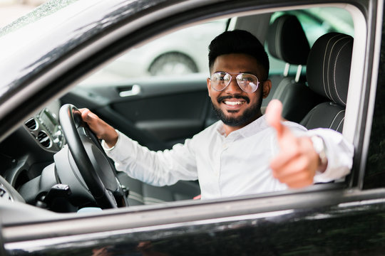 Young asian indian man showing thumbs up while driving car