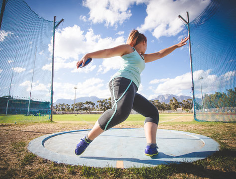 Wide angle action photo of a female discus athlete throwing a discus
