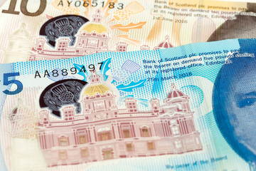 detail of 5 and 10 Pounds Sterling notes issued by Bank of Scotland