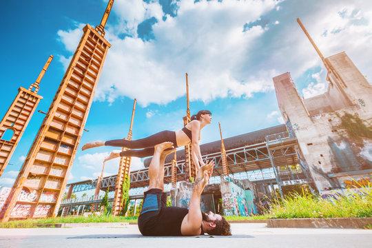Scenario urbano con coppia di giovani che fa acroyoga e yoga