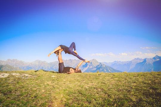Giovane coppia pratica acroyoga e yoga all'aperto in montagna al parco