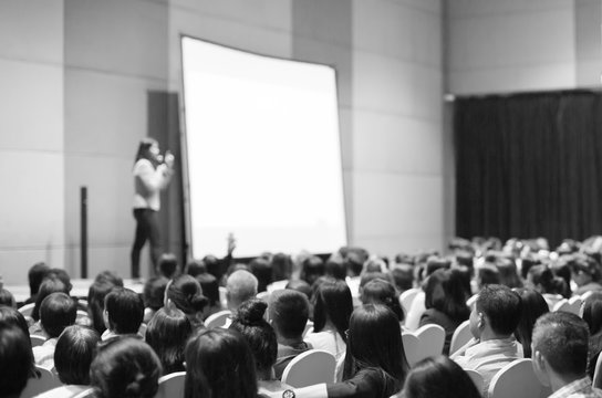 Seminar presenter at corporate conference giving speech. Woman speaker giving lecture to forum audience. Female executive manager leading discussion during technology company training event.