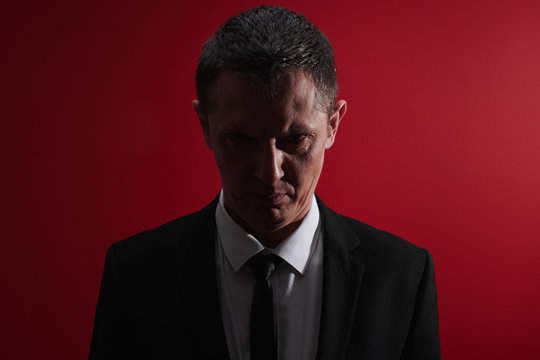 The evil boss. Portrait of an angry man in a business suit with red eyes with rage. Aggressive person